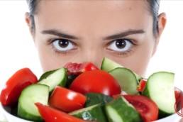 Dame die über eine Salatschüssel schaut und sich wundert, ob man trotz Diät nicht abnehmen kann.