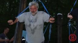 Herr im Wald beim funktionellen Krafttraining im alter, und dem ausführen einer TRX Liegestütze