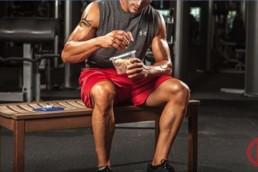 Fitter Typ sitzt im Gym und mischt seinen Proteinshake